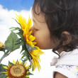Cute girl smelling sunflowers — Stock Photo #9549630