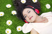 Beautiful woman listens to music outdoor — Stock Photo