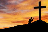 Man praying under the cross — Stock Photo