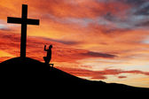 Silhouette of a man praying under the cross — Stock Photo