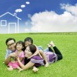Stock Photo: Young AsiFamily with dream house on field