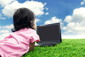 Little girl with laptop outdoor — Stock Photo