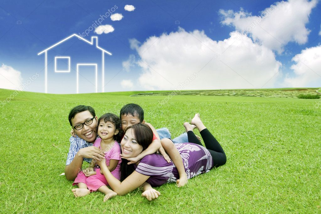 Happy family  posing on field with a drawn house in background — Stock Photo #9924622