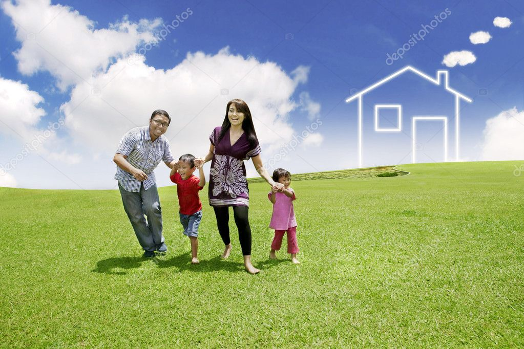 Happy family  playing on field with a drawn house in background  Stock Photo #9924687
