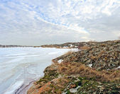 Zima, zamarznięte jezioro, skalisty brzeg — Zdjęcie stockowe
