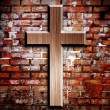 Wooden crucifix on the brick wall lighting by spotlight - Stockfoto