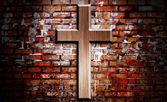 Wooden crucifix on the brick wall lighting by spotlight — Stock fotografie