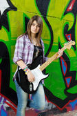 Closeup portrait of a young girl with guitar against graffiti ba — Stock Photo