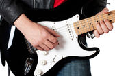 Young guy in leather jacket playing electric guitar — Stock Photo