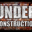 Under Construction on brick wall — Stock Photo
