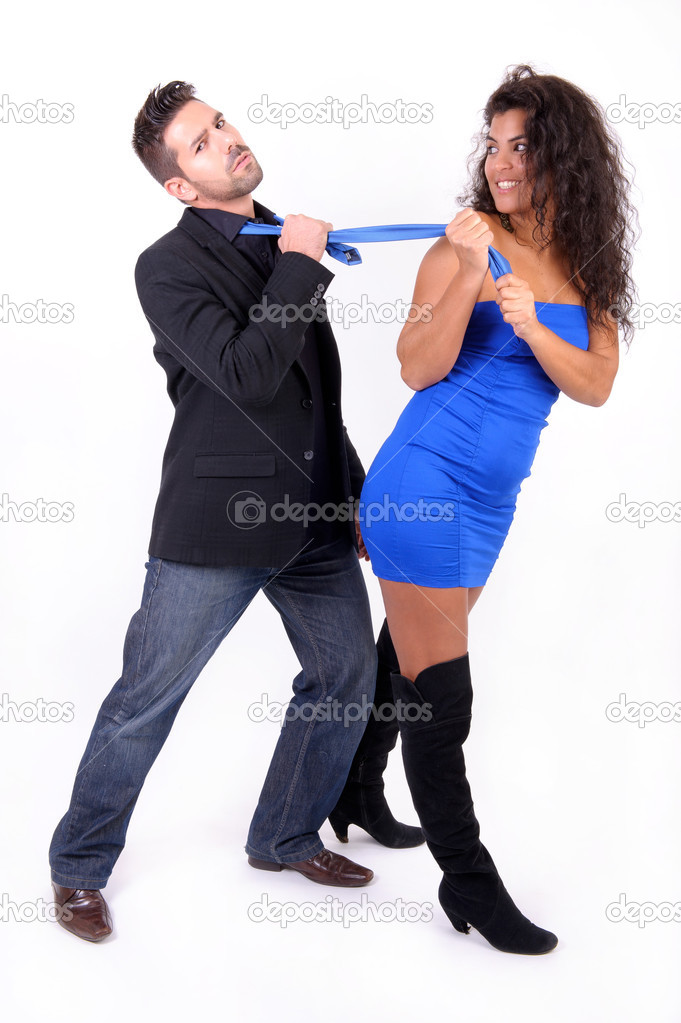 Brunette woman in blue dress dragging a man with his blue tie — Stock Photo #9126921