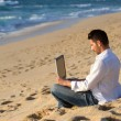 Working in the laptop at the beach — Stock Photo