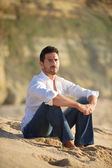 Smiling man seated on the sand — Stock Photo