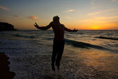 Silhouette of a man jumping at the beach — Stock Photo