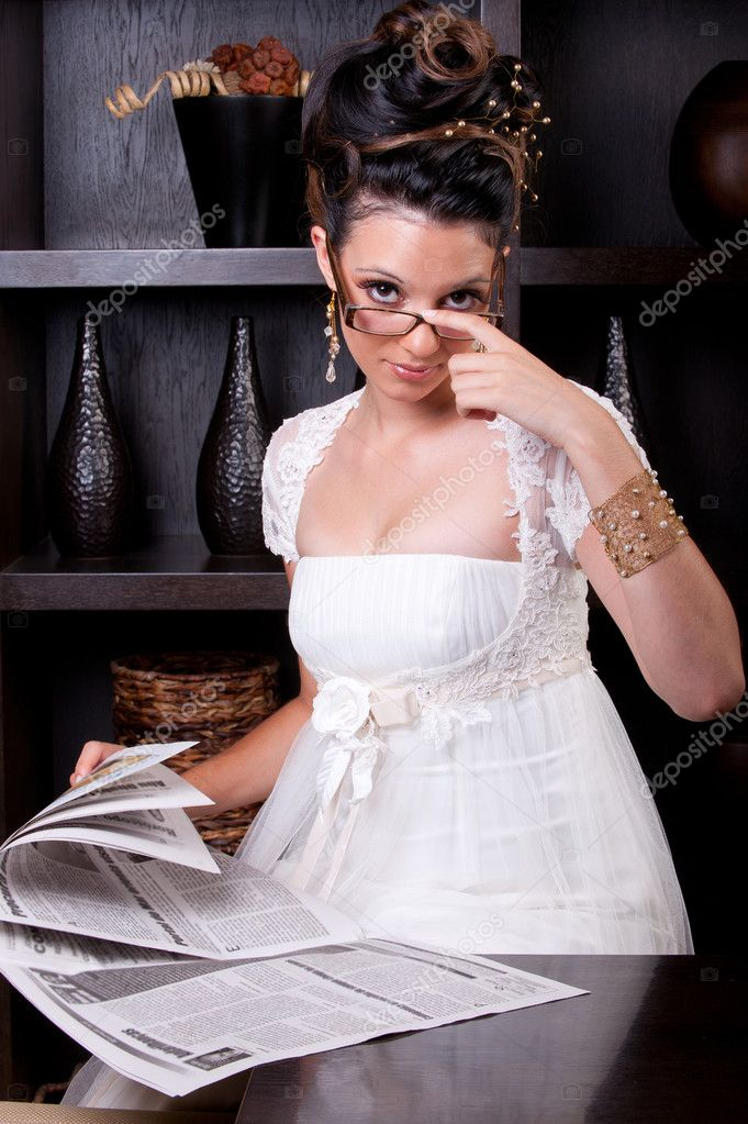 Beautiful brunette in glasses reading the newspaper — Stock Photo #9550192