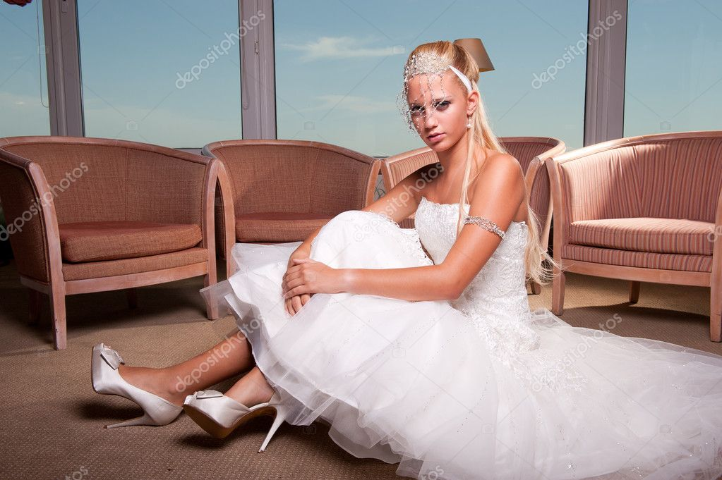 Beautiful young blonde bride seated on the hotel floor — Stock Photo #9550651