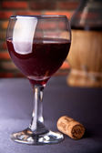 Red wine in glass with cork — Stock Photo