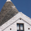 Trulli roof against vivid blue sky - Stock Photo