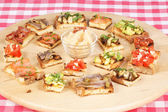 Various italian bruschetta over a wooden cutting board — Stock Photo