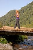 Beautiful girl walking on a wooden bridge — Stock Photo