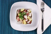 Octopus with potatoes served in a white dish — Stock Photo
