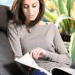 Close-up of a young woman lying on a sofa reading a magazine. — Stock Photo
