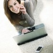 Smiling woman using her laptop in the living room. — Stock Photo #10302256