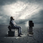 Businessman with gas mask watching TV — Stock Photo