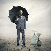 Global Warming:Businessman waiting for the rain — Stock Photo