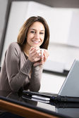Young woman with a cup of coffee and laptop — Stock Photo