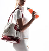 Athletic woman with a sports bag and sports drink — Stock Photo