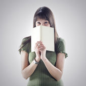 Woman hides behind a book . cover is blank — Stock Photo