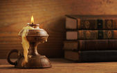 Old candle on a wooden table, old books in the background — Stock Photo