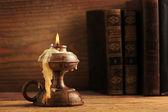 Vela velha sobre uma mesa de madeira, velha livros em segundo plano — Foto Stock