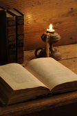 Old book on a wooden table by candlelight — Stock Photo
