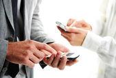 Mensaje de texto de empresarios en sus teléfonos móviles — Foto de Stock