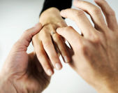 Man putting a ring with a brilliant on a female hand, love conc — Stock Photo