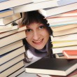 Young woman behind a big pile of books — Stock Photo