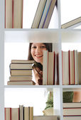 Young Woman looking for a book at the library , similar photo on — Foto de Stock