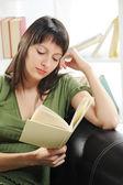 Porträtt av en ung kvinna med bok, bokhylla på bakgrunds — Stockfoto