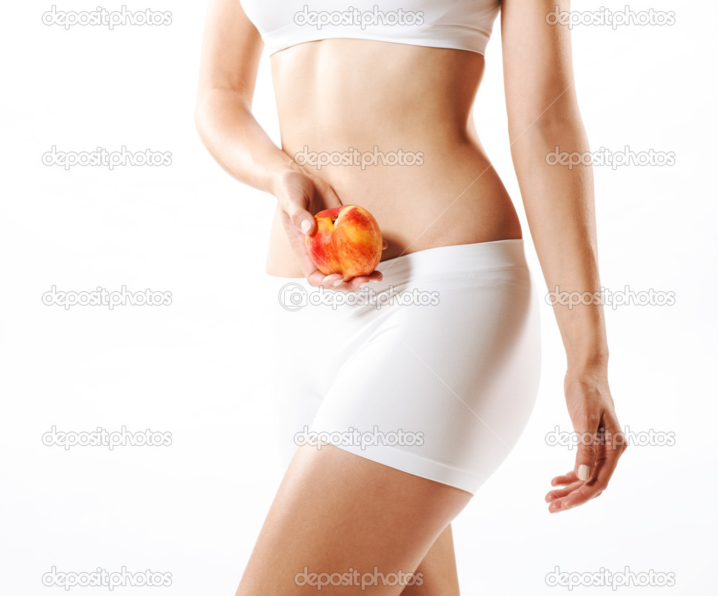 Fit young woman holding a peach, shot on white  Stock Photo #8504051
