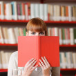 Girl hiding behind the book on library — Stock Photo #8737006