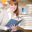Young college student in a library — Stock Photo