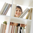 Young Woman looking for a book at the library — Stock Photo