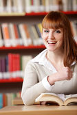 Portrait of a smiling caucasian teen girl at library — Stock Photo