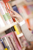 Young woman looking for a book in a bookstore - hand close up — Stock Photo