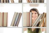 Ung kvinna söker en bok på biblioteket — Stockfoto