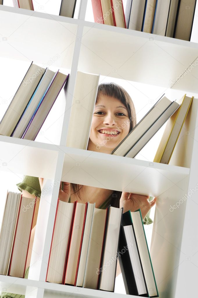 Young Woman looking for a book at the library — Stock Photo #8737636