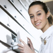 Stock Photo: Young female pharmacist reaching for medicine