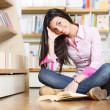 Smiling female college student sitting on floor in library, read — Stock Photo